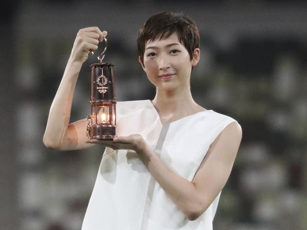 Rikako Ikeeová drží lampáš s olympijským ohňom
