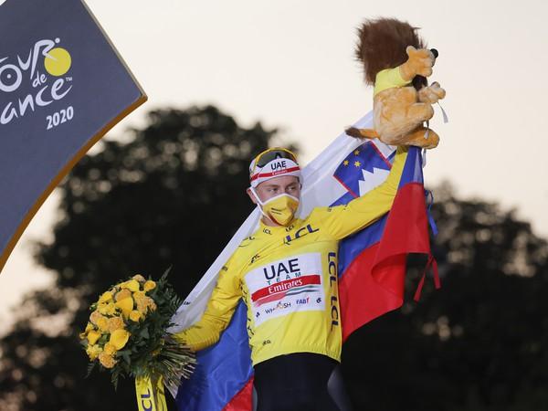 Tadej Pogačar oslavuje na pódiu v žltom drese celkové víťazstvo na Tour de France