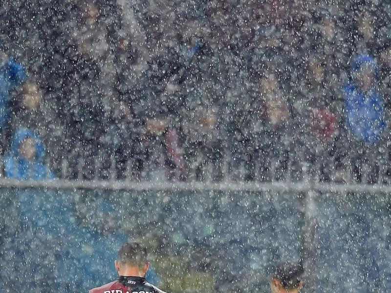 Davide Biraschi a rozhodca Rosario Abisso opúšťajú hraciu plochu počas prudkého lejaku