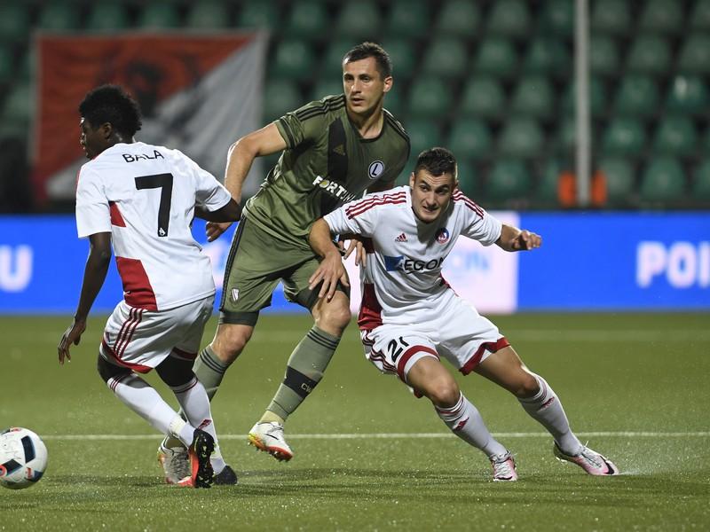 Uprostred hráč Legie  Tomasz Jodlowiec medzi hráčmi Trenčína, vľavo Aliko Bala a vpravo Matúš Bero