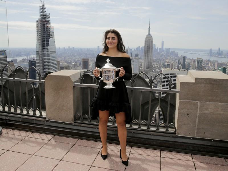 Bianca Andreescuová pózuje s trofejou za US Open a na dlani má celý New York