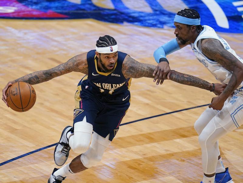 Hráč New Orleans Pelicans Brandon Ingram (vľavo) dribluje cez Kentaviousa Caldwella-Popeho z Los Angeles Lakers