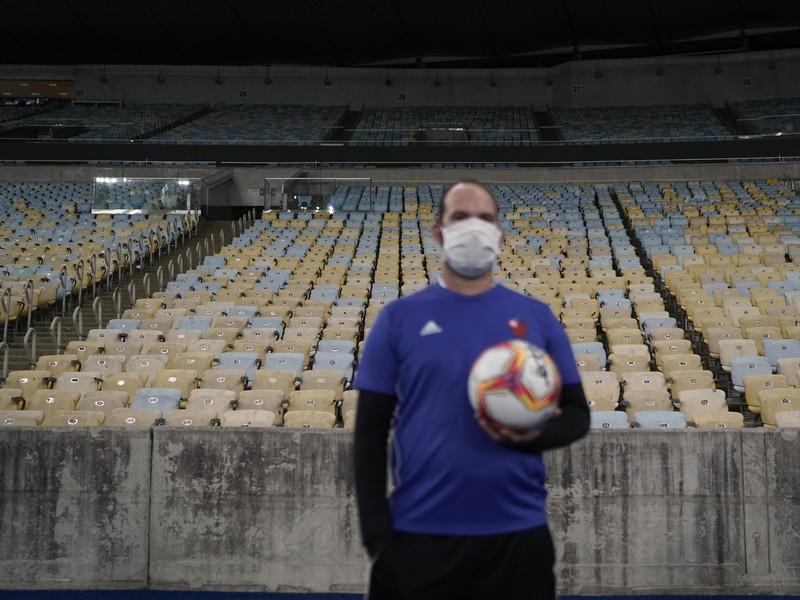 Podávač lôpt stojí pred prázdnymi tribúnami na štadióne Maracana