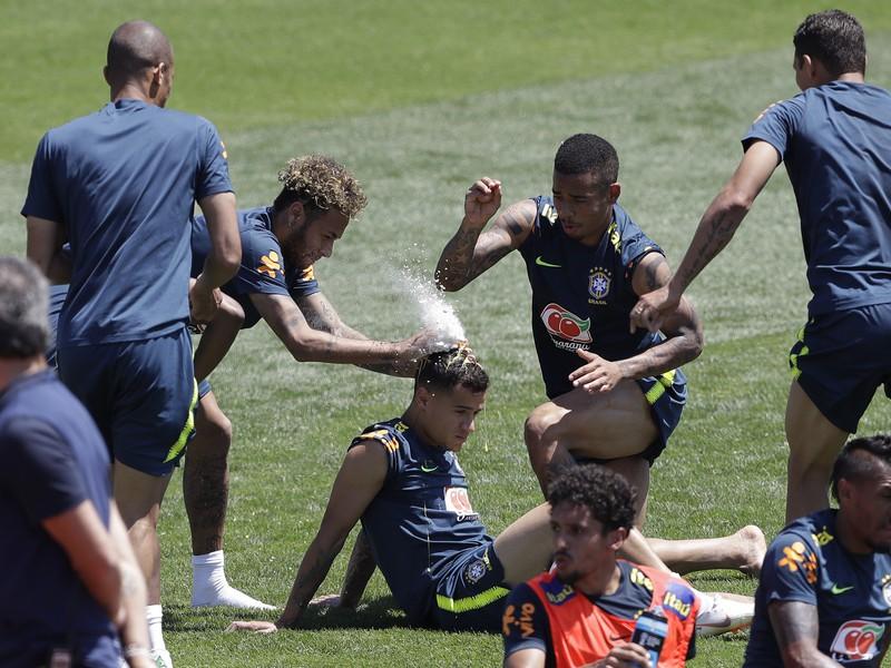 Brazílski futbalisti Neymar (vľavo) a Gabriel Jesus hádžu múku a vajíčka na hlavu spoluhráča Philippe Coutinha, ktorý oslavuje svoje narodeniny počas tréningu v Soči