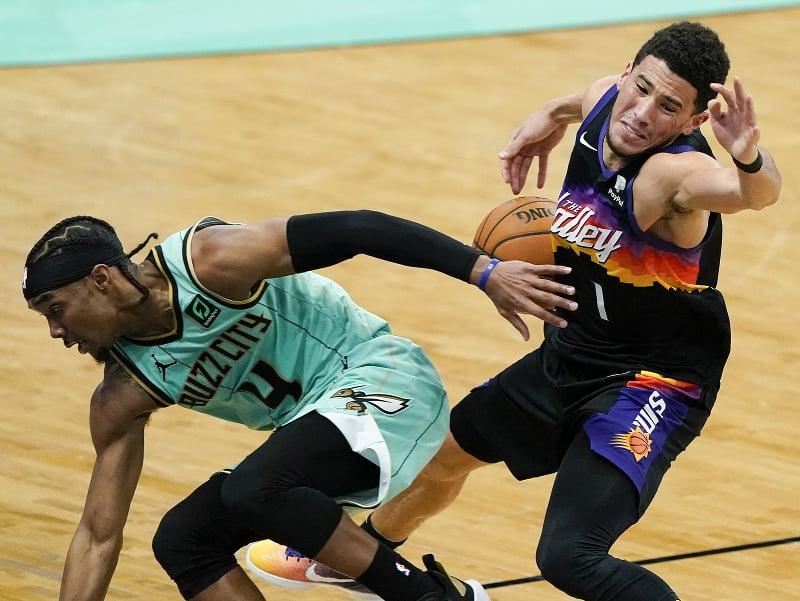 Devonte' Graham (vľavo) zo Charlotte Hornets a Devin Booker z Phoenixu Suns v súboji o loptu