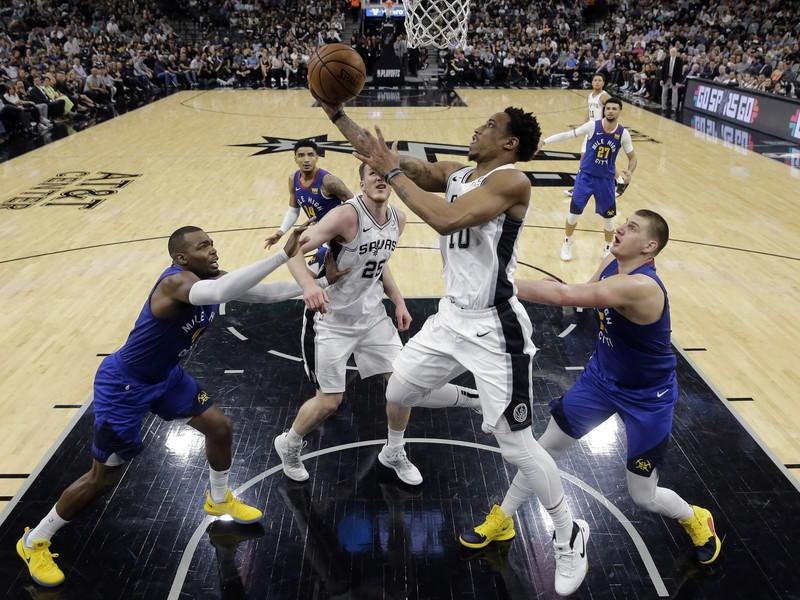 Hráč San Antonia Spurs DeMar DeRozan (hore uprostred) strieľa na kôš cez  Nikolu Jokiča (vpravo)