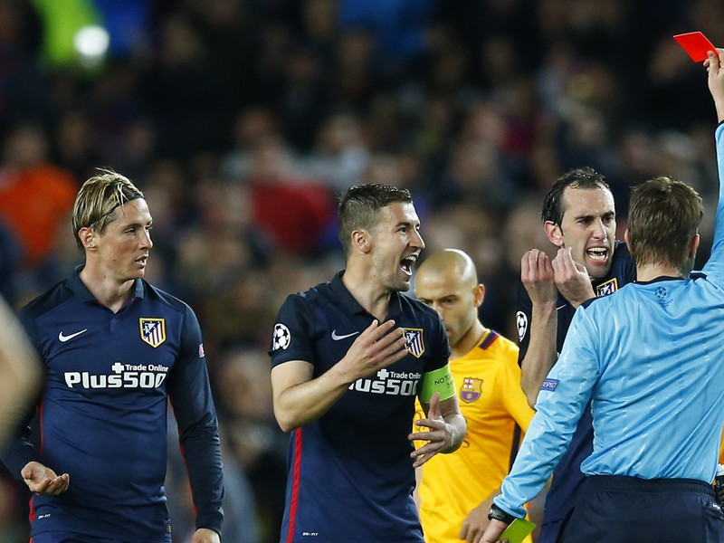 Rozhodca Felix Brych udeľuje Torresovi červenú kartu a futbalisti Atlética protestujú