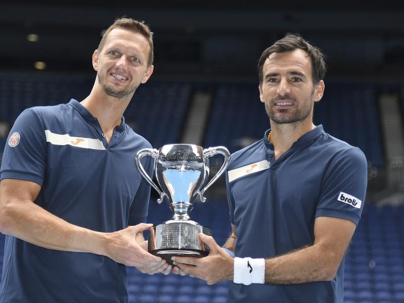 Slovensko-chorvátska dvojica Filip Polášek a Ivan Dodig pózuje s trofejou po víťazstve vo finále mužskej štvorhry