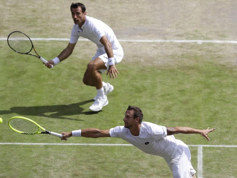 Filip Polášek a Ivan Dodig bojujúci na Wimbledone