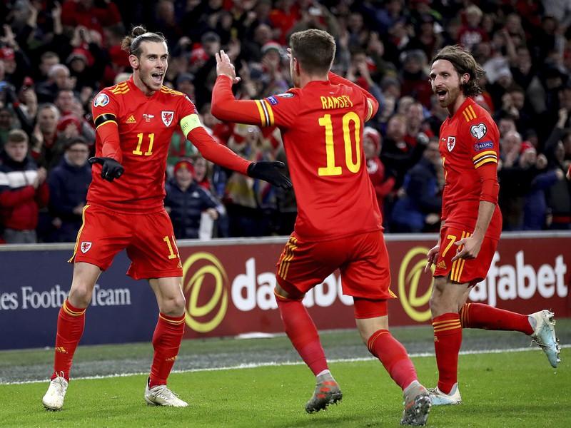 Na snímke v strede hráč Walesu Aaron Ramsey oslavuje so spoluhráčmi Garethom Baleom (vľavo) a Joe Allenom (vpravo) svoj úvodný gól v zápase 10. kola E-skupiny kvalifikácie na EURO 2020 Wales - Maďarsko