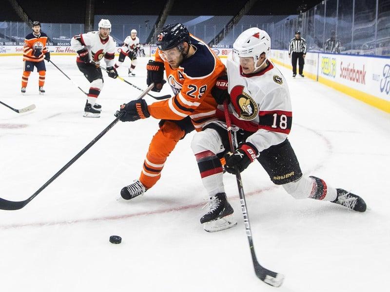Leon Draisaitl, ktorý prispel k víťazstvu Edmontonu Oilers šiestimi asistenciami, na snímke bojuje o puk s Timom Stuetzle