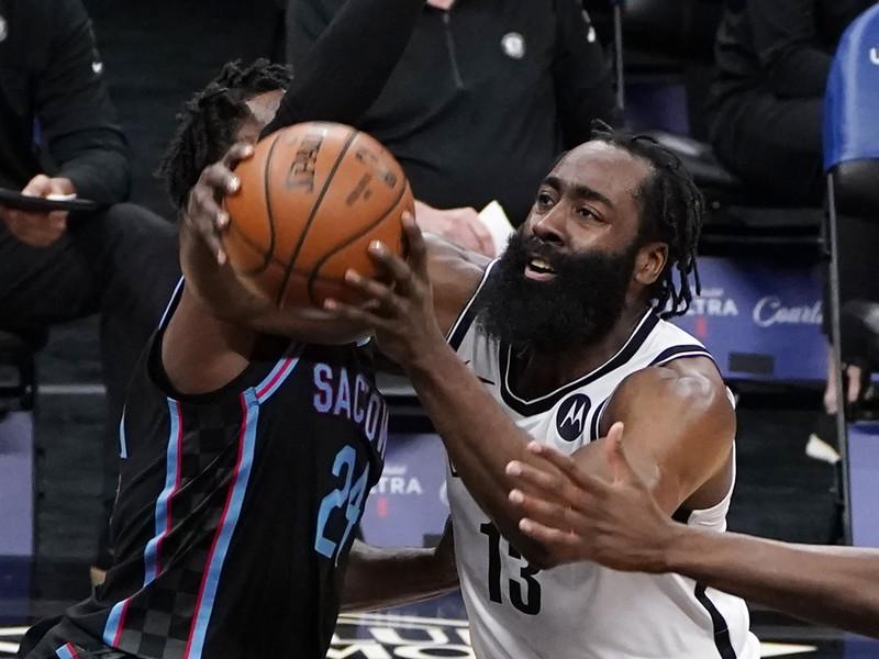 Na snímke vpravo hráč Nets James Harden, vľavo hráč Kings Buddy Hield v zápase basketbalovej NBA