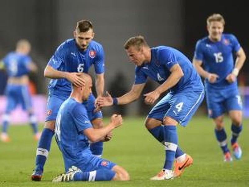 Martin Jakubko (dole) sa teší z gólu s Jánom Ďuricom (druhý sprava) a Norbertom Gyömbérom počas prípravého futbalového zápasu Izrael - Slovensko