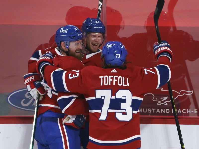 Eric Staal (v strede) oslavuje gól s Jeffom Petrym (vľavo) a Tylerom Toffolim