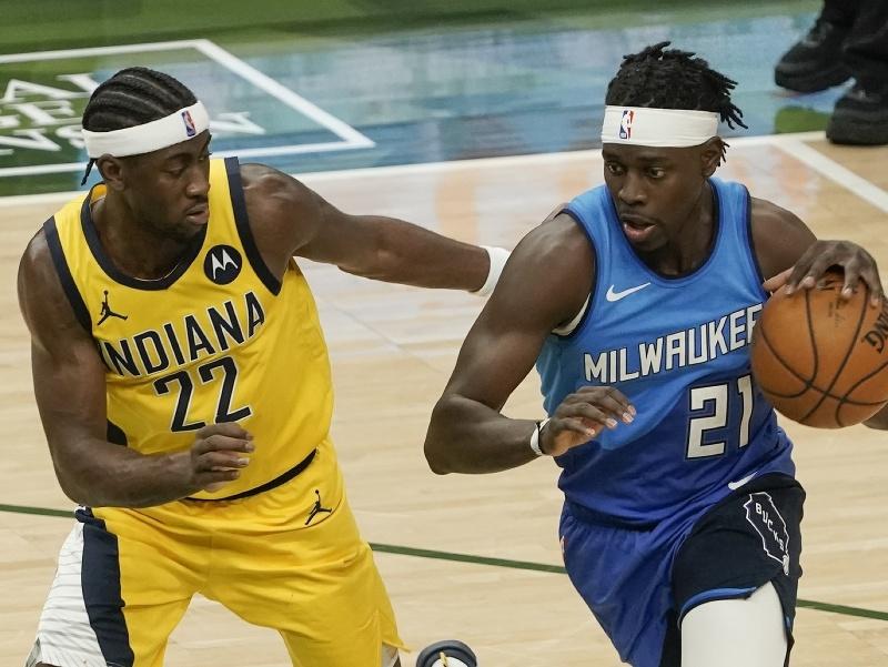 Hráč Milwaukee Bucks Jrue Holiday (vpravo) v súboji s Carisom LeVertom z  Indiany Pacers