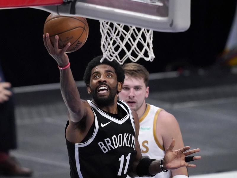 Hráč Brooklynu Nets Kyrie Irving  (vľavo) strieľa na kôš cez Luka Dončiča z Dallasu Mavericks