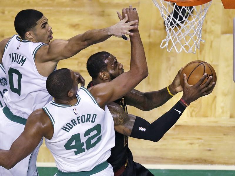 Hráči Bostonu Celtics Jayson Tatum (0) a Al Horford (42) sa pokúšajú zastaviť LeBrona Jamesa z Clevelandu Cavaliers (vpravo)