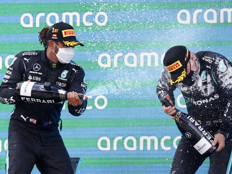 Valtteri Bottas a Lewis Hamilton oslavujú na stupni víťazov