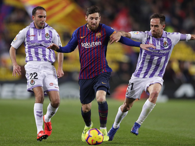 Futbalista FC Barcelony Lionel Messi (uprostred), hráči Valladolidu