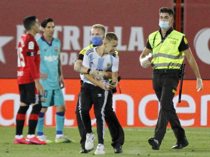 Narušiteľ zápasu na ihrisku, v pozadí Lionel Messi