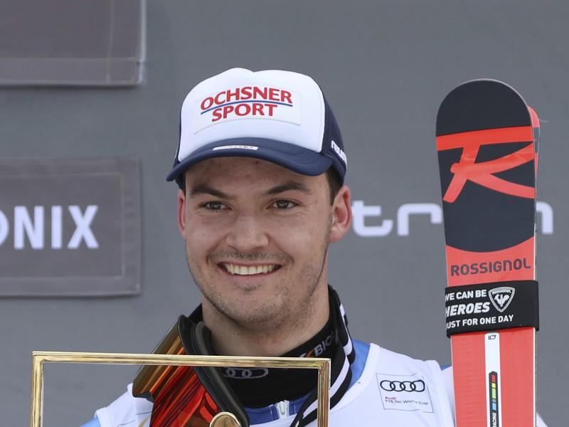 Švajčiarsky lyžiar Loic Meillard pózuje na pódiu po víťazstve v nedelňajšom paralelnom obrovskom slalome