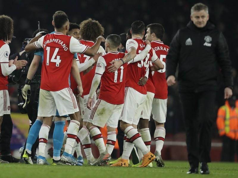 Ole Gunnar Solskjaer, v pozadí radujúci sa hráči Arsenalu