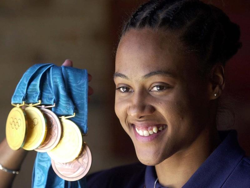 Na archívnej snímke z 1. októbra 2000 v Sydney americká atlétka Marion Jonesová ukazuje svojich päť olympijských medailí.