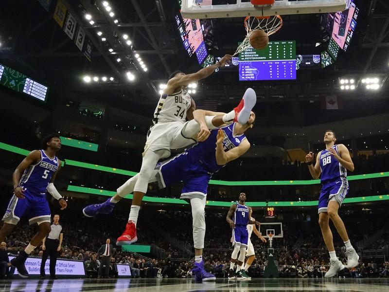 Hráč Milwaukee Bucks Giannis Antetokounmpo (hore) smečuje na kôš cez Kosta Koufosa zo Sacramenta Kings