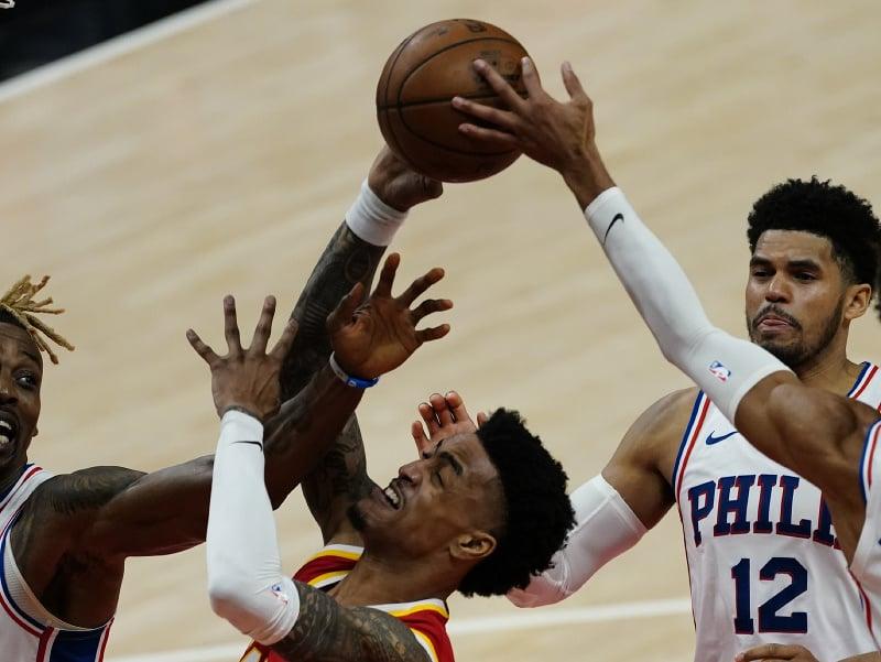 John Collins zastavený obrancami Philadelphie počas zápasu NBA