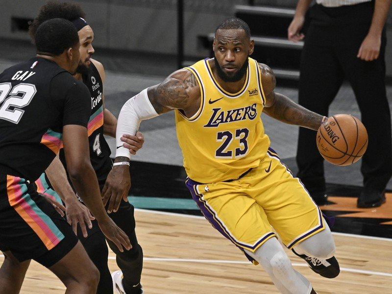 LeBron James vedie loptu cez dvoch hráčov Spurs