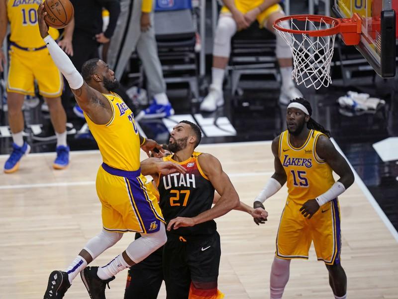 Hráč Los Angeles Lakers  LeBron James (vľavo) strieľa na kôš cez Rudyho Goberta z Utahu Jazz