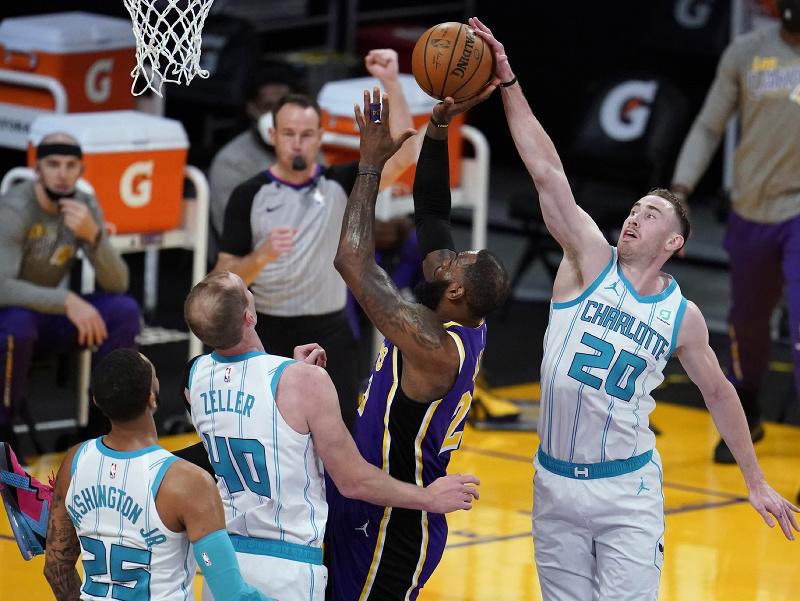 Útočník Gordon Hayward (20) z Charlotte Hornets a hráč LeBron James z Los Angeles Lakers v súboji o loptu