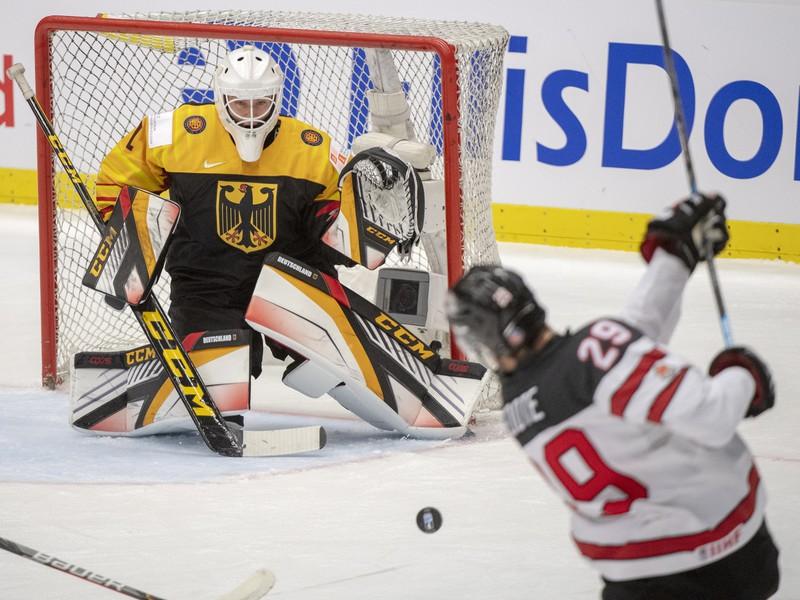 Kanadský hokejista Nolan Foote strieľa na nemeckého brankára Hendrika Haneho