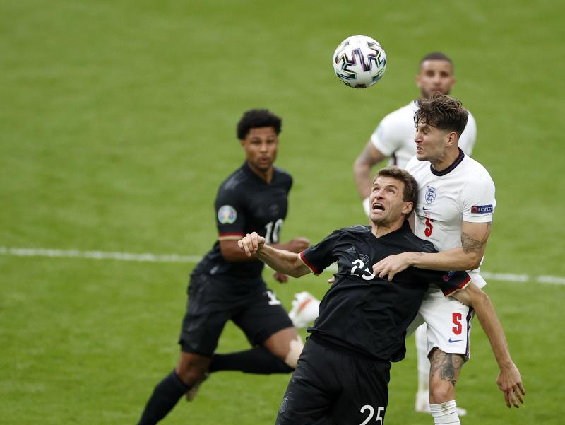 Thomas Müller v hlavičkovom súboji s Johnom Stonesom