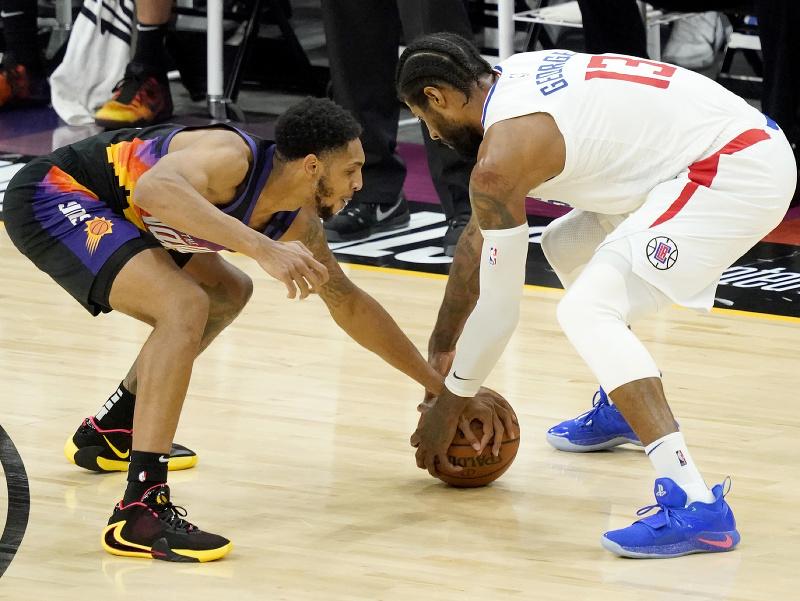 Hráč Los Angeles Clippers Paul George (vpravo) bojuje o loptu s Cameronom Payneom z Phoenixu Suns
