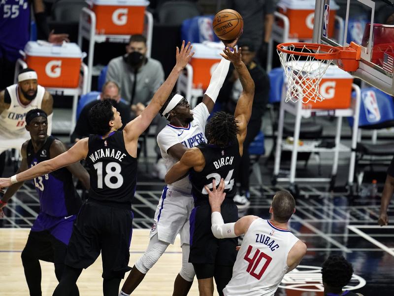 Hráč Los Angeles Clippers  Reggie Jackson (uprostred) strieľa na kôš