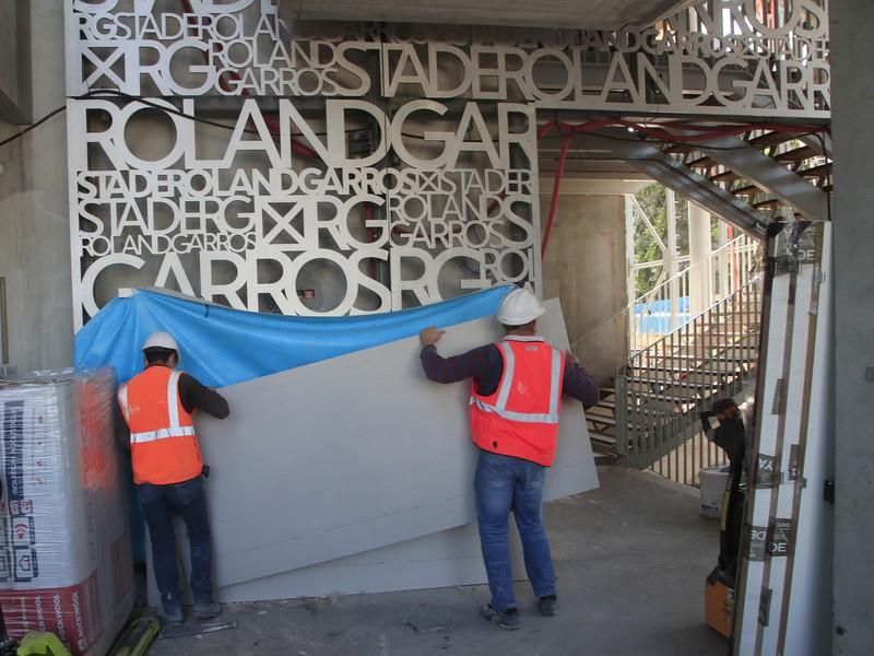 Robotníci nesú dosku na hlavnom tenisovom dvorci Philippa-Chatriera v tenisovom aréali parížskeho Roland Garros