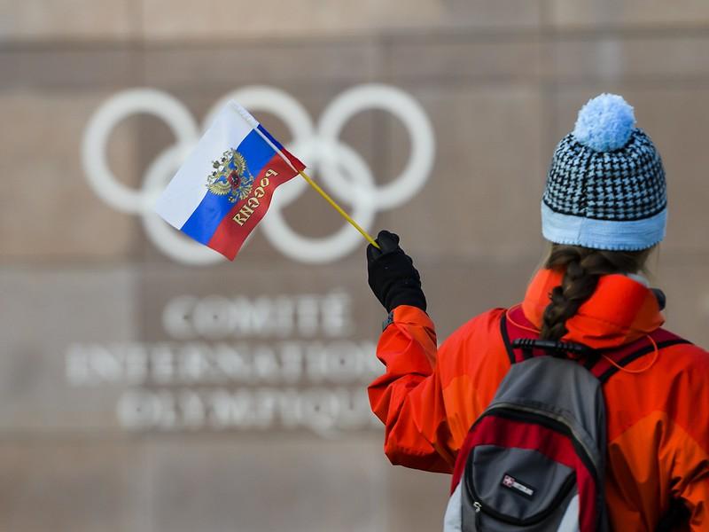 Žena drží ruskú zástavu pred vstupom do sídla Medzinárodného olympijského výboru