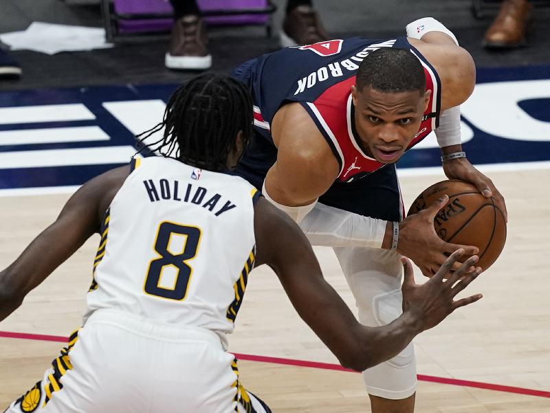Hráč Washingtonu Wizards Russell Westbrook (vpravo) sa pokúša strieľať cez Justina Holidaya z Indiany Pacers