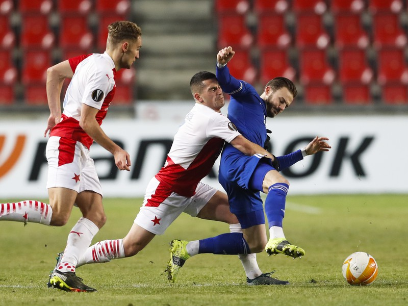 Futbalista Slavie Praha Nicolae Stanciu (uprostred) a hráč Leicesteru James Maddison bojujú o loptu