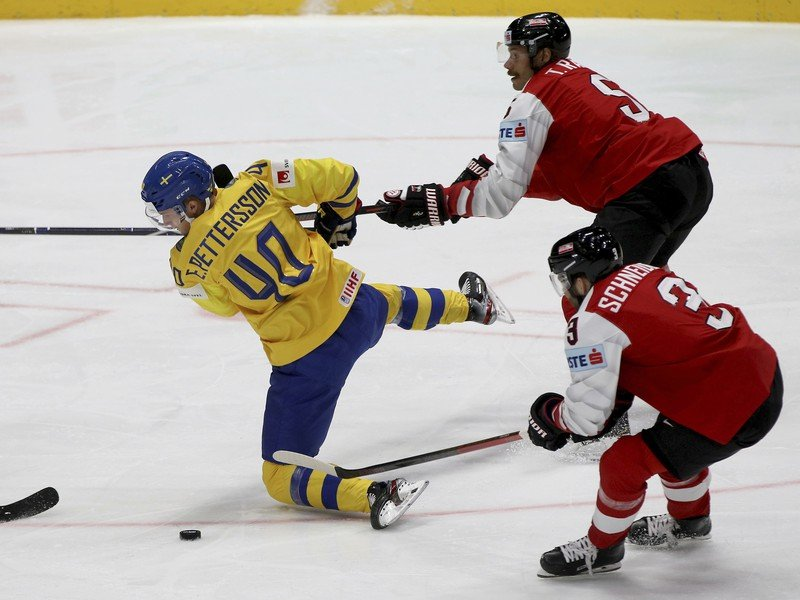 Elias Pettersson, left, checks Austria's Thomas Raffl and Peter Schneider,