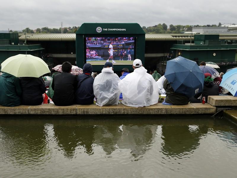 Diváci na Wimbledone sledujú zápas pod dáždnikmi