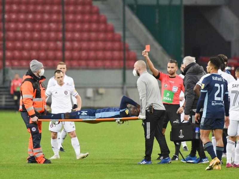 Na snímke zranený hráč Slovana na nosidlách Myenty Abena dostáva červenú kartu za faul od rozhodcu Filipa Glovu