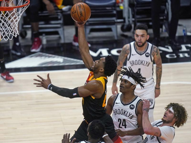 Hráč Utahu Jazz Donovan Mitchell (vľavo) strieľa na kôš cez Alizea Johnsona (24) a Tylera Johnsona (vpravo) z Brooklynu Nets